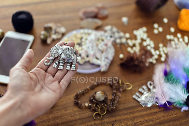 Close-up of female hand holding elephant figurine for handicraft — Fotografia de Stock