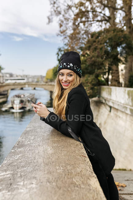 Paris, France, tourist woman with smartphone near Seine river, smiling at camera — Stock Photo