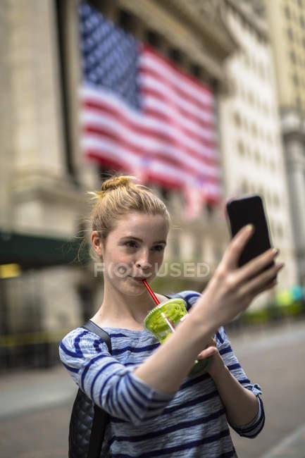 Портрет молодой женщины, делающей селфи со смузи — стоковое фото