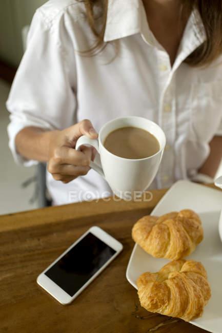 Donna con caffè, croissant e cellulare a tavola — Foto stock