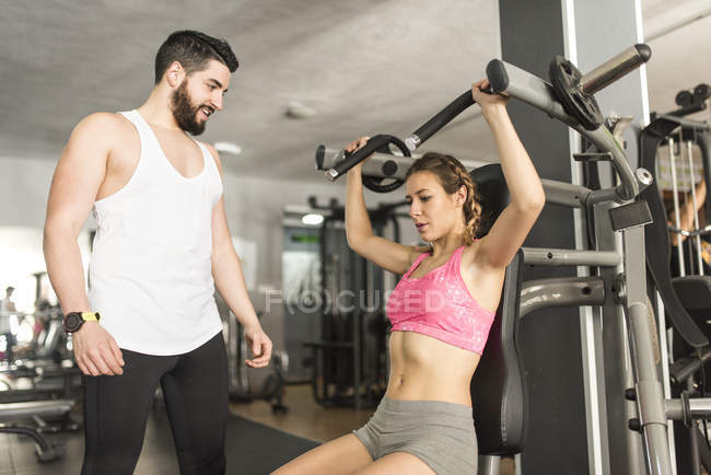 Sporty caucasian coach training woman in gym — Stock Photo