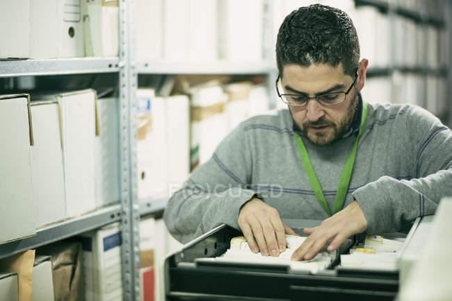 Mann auf der Suche nach Dateien in einem Archiv — Stockfoto