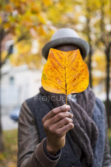 Mann mit verdunkeltem Gesicht mit Herbstblatt — Stockfoto