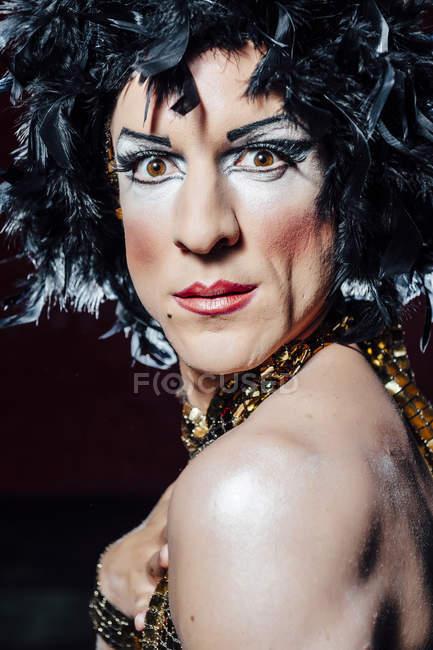 Acteur habillé comme une fille avec un visage étonnant sur fond noir — Photo de stock