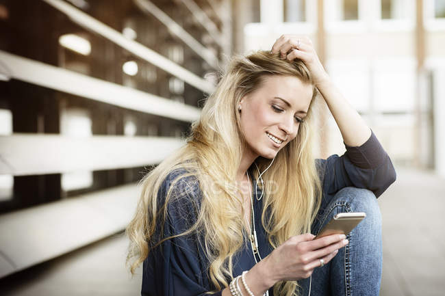 Smiling blond young woman with earphones using cell phone — Stock Photo