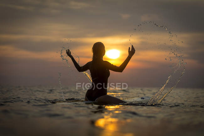 Surferin planscht bei Sonnenuntergang im Ozean — Stockfoto