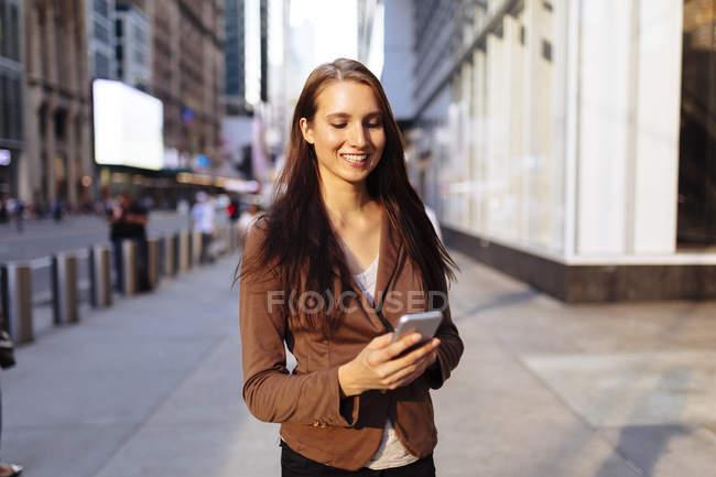 Junge Geschäftsfrau mit Smartphone in der Manhattan Street. New York City. uns — Stockfoto