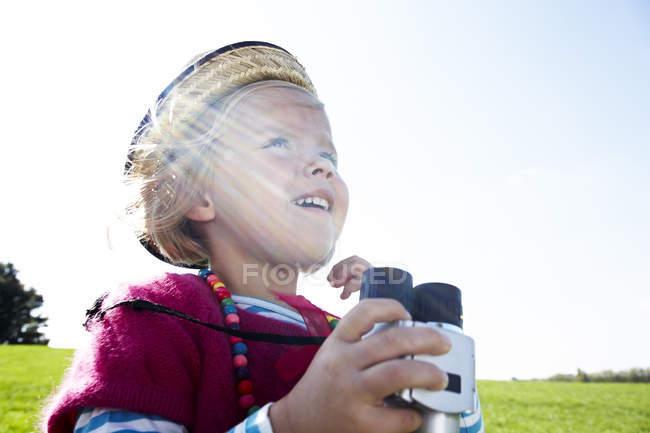 Menina loira feliz com binóculos no prado — Fotografia de Stock