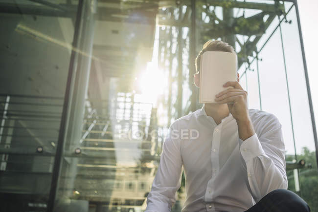 Retrato do empresário fechando o rosto com notebook — Fotografia de Stock