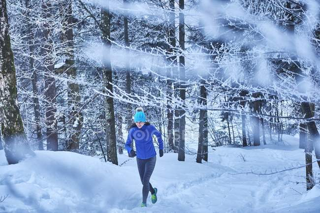 Alemania, Baviera, Jochberg, mujer a correr por el bosque de invierno - foto de stock