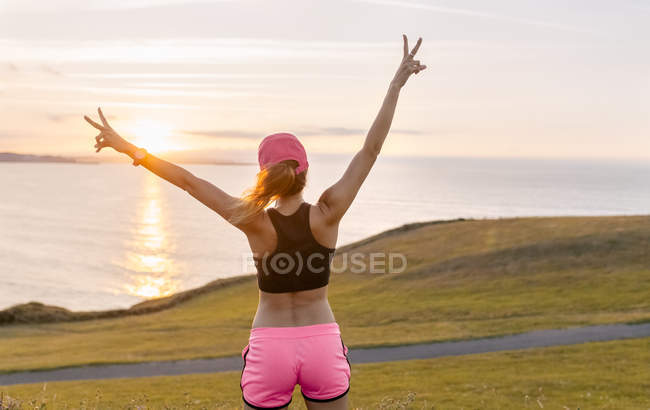 Woman standing with arms outstretched — Stock Photo