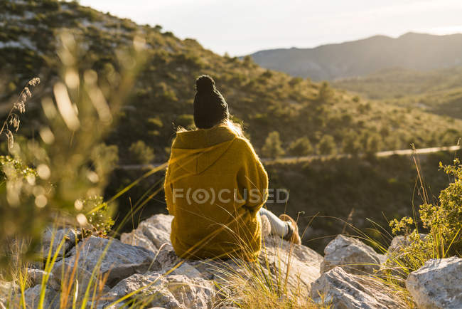 Woman sitting on rock in nature — Stock Photo