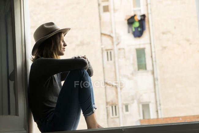 Молодая женщина, сидя на подоконнике на дому — стоковое фото