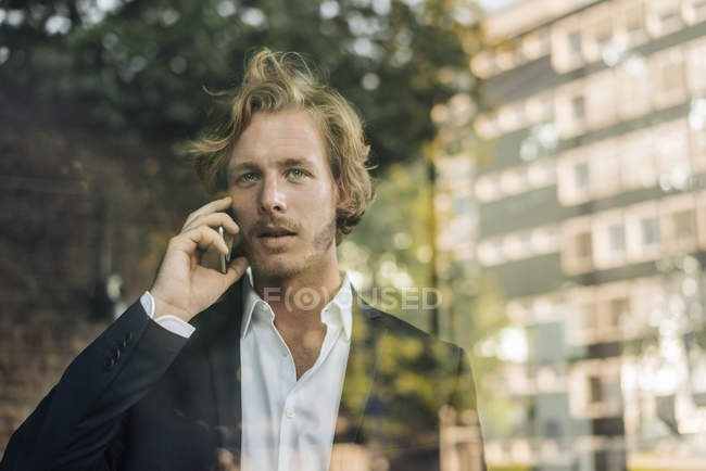 Businessman on cell phone standing behind windowpane — Stock Photo