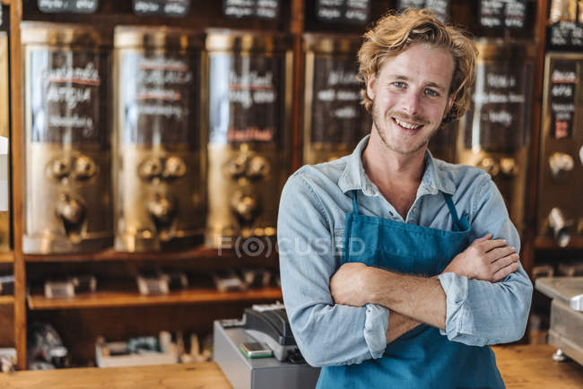 Portrait of smiling coffee roaster standing in shop with arms crossed — Stock Photo