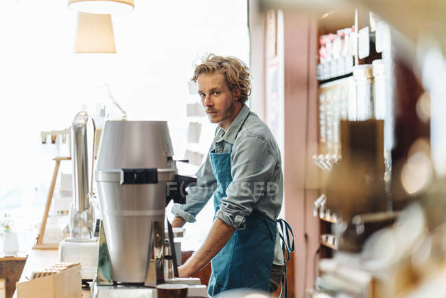 Portrait of coffee roaster standing at counter in shop and looking at camera — Stock Photo
