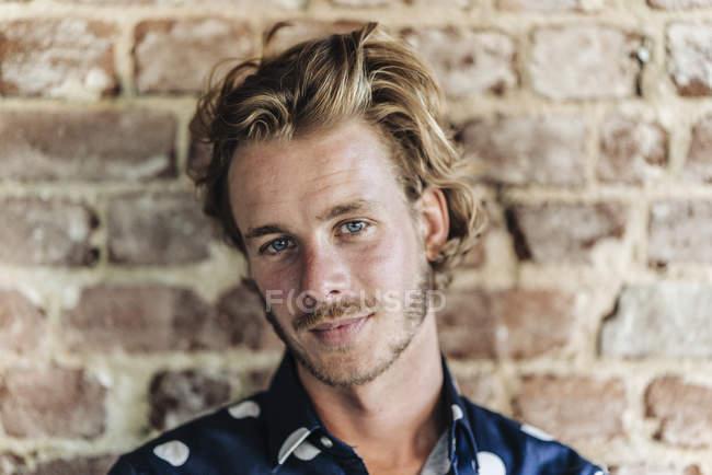 Portrait d'homme funky blond confiant debout devant un mur de briques — Photo de stock