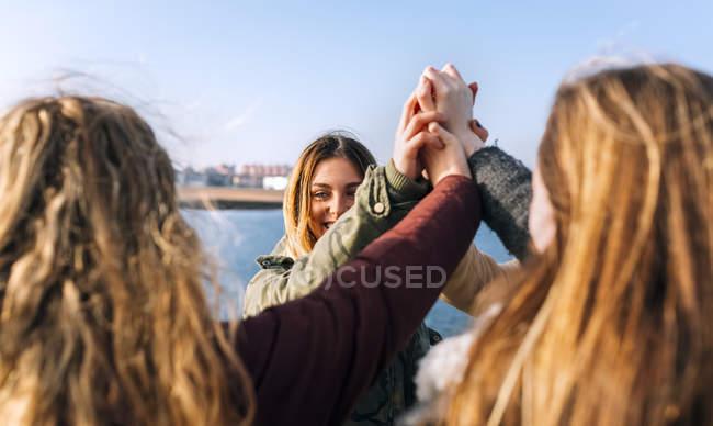 Quattro amici che unisce le mani in città — Foto stock
