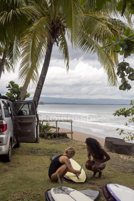 Indonésie, Java, deux femmes préparant une planche de surf sur la côte — Photo de stock