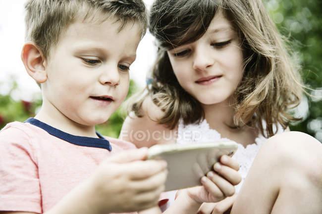Брат и сестра с помощью смартфона — стоковое фото