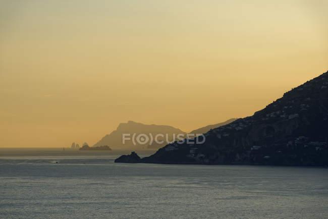 Вид на скелі над морською водою в сутінках — стокове фото