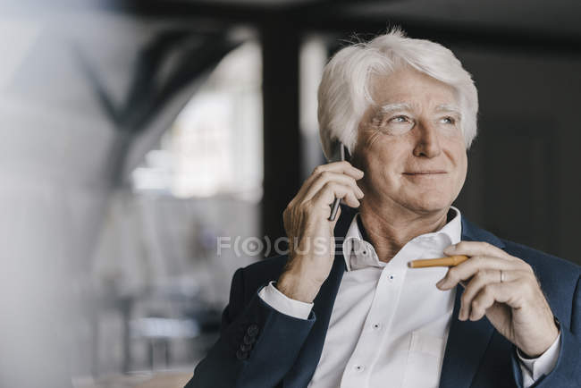 Portrait of senior businessman using mobile phone in office — Stock Photo