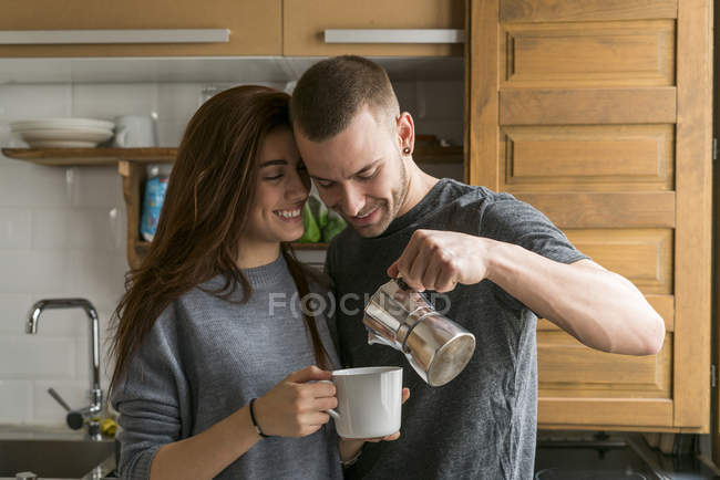 Couple standing in kitchen with coffee — Stock Photo