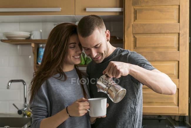 Pareja de pie en la cocina con café - foto de stock