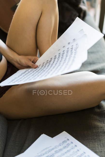 Junge Frau hält Notenblätter mit Noten zu Hause — Stockfoto