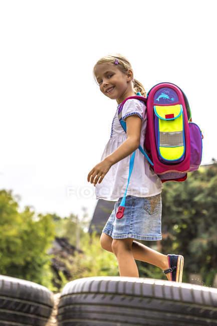 Menina sorridente com saco de escola no recreio — Fotografia de Stock