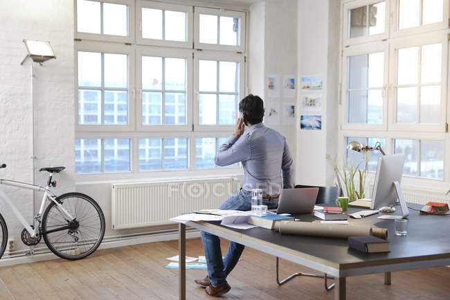Man using cell phone in a modern informal office — Stock Photo
