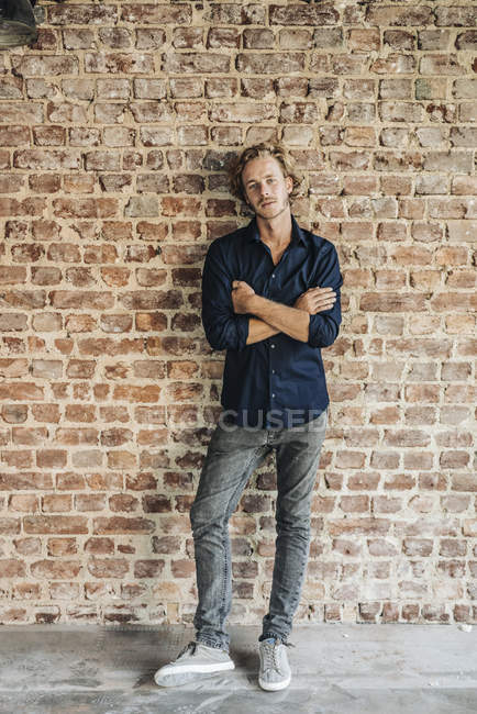 Portrait of man standing with arms crossed in front of brick wall — Stock Photo