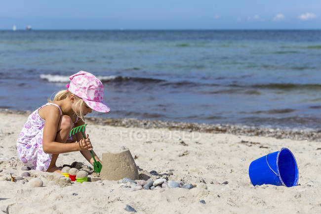 Маленькая девочка играет на пляже с песком — стоковое фото