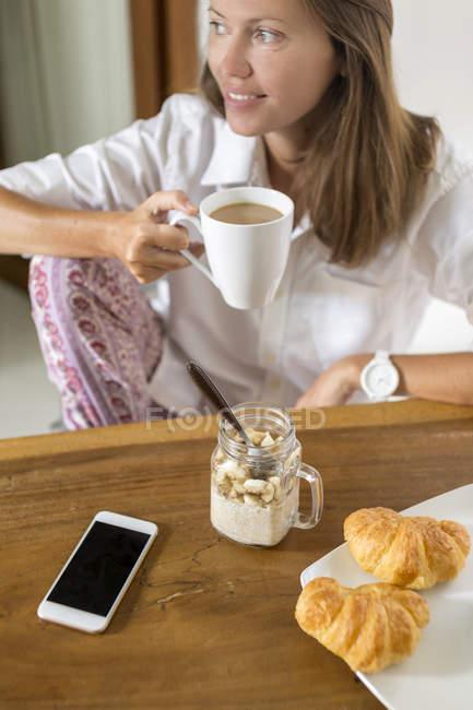 Donna sorridente seduta con una tazza di caffè a tavola — Foto stock