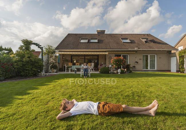 Ragazzo adolescente sdraiato in giardino con casa sullo sfondo — Foto stock