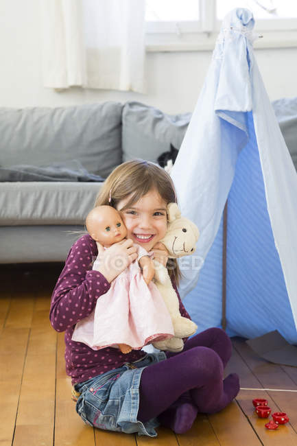 Portrait of happy little girl with toys at home — Stock Photo