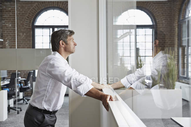 Businessman in office standing at glass pane — Stock Photo