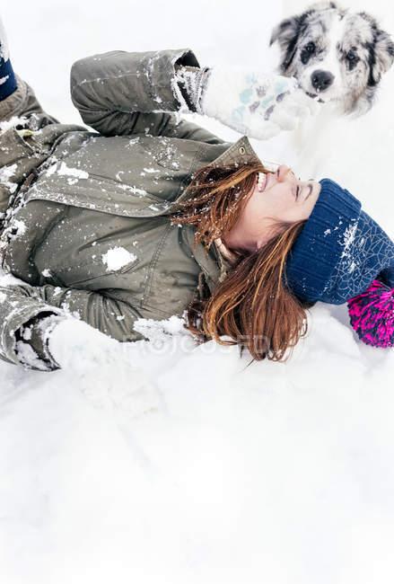 Jeune femme jouant avec son Colley de frontière dans la neige — Photo de stock