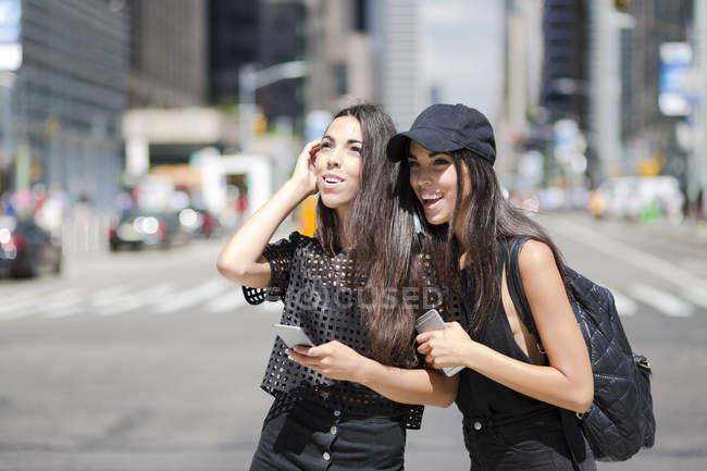 Irmãs gêmeas com celulares na cidade — Fotografia de Stock