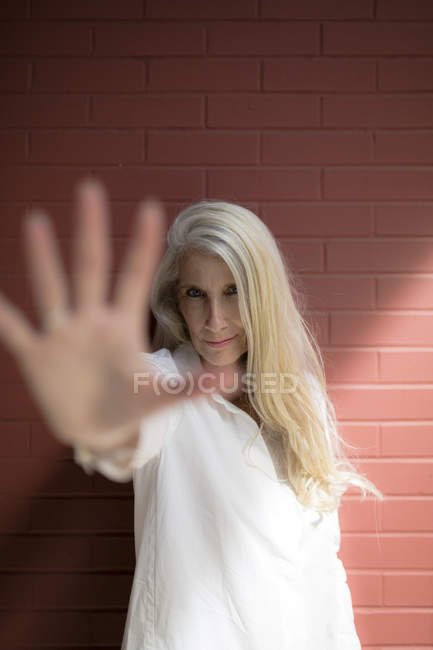 Portrait of senior woman showing hand — Stock Photo