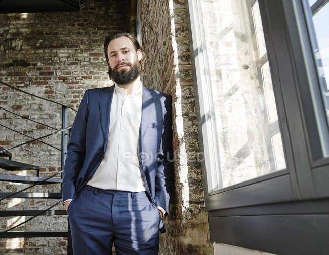 Бизнесмен стоит в современном офисе — стоковое фото