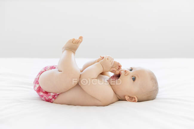 Baby lying on back on white bed and holding foot in mouth — Stock Photo
