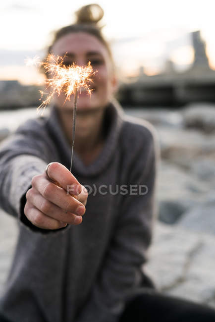 Girl with burning sparkler in hand — Stock Photo