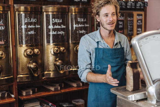 Coffee roaster weighing coffee in shop — Stock Photo