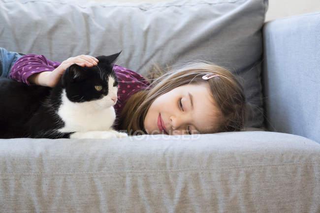 Menina deitada no sofá e acariciando o gato — Fotografia de Stock