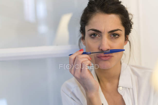 Portrait of woman with ballpen pouting mouth — Stock Photo