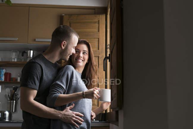 Paar mit Cup im Dachgeschoss Küche am Fenster — Stockfoto