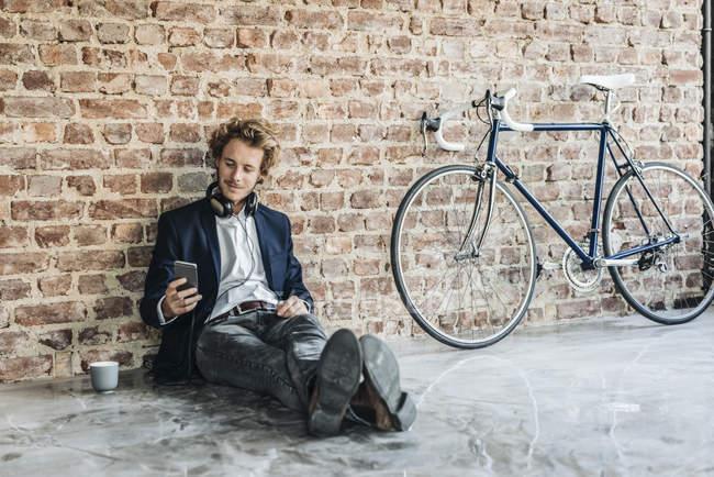 Человек в наушниках, сидящий на полу и использующий мобильный телефон — стоковое фото