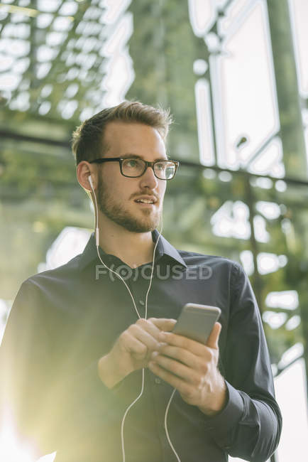Portrait of businessman using smartphone and earbuds — Stock Photo