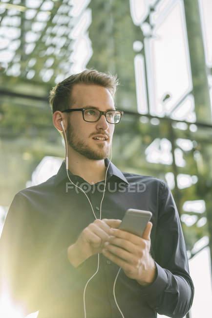 Портрет предпринимателя с помощью смартфона и вкладыши — стоковое фото